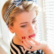 Closeup picture of cute blond young woman pinup girl with red lips and nails looking down dreaming on jalousie sun lighting windows background portrait — Stock Photo #51540971
