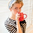 Image of pretty blond young pin up woman with red lips nails drinking coffee or tea holding red cup & looking at camera on white jalousie sun lighted background closeup portrait — Stock Photo #51541057