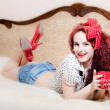 Portrait of holding red cup of hot drink sexy pin-up girl beautiful redhead young woman with red lips and nails happy smiling & looking at camera relaxing in bed — Stock Photo #51541105