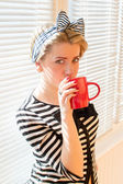 Image of pretty blond young pin up woman with red lips nails drinking coffee or tea holding red cup & looking at camera on white jalousie sun lighted background closeup portrait — Stock Photo
