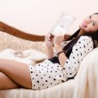 Closeup portrait of beautiful brunette young woman in polka dot dress pinup girl having fun holding book happy smiling & looking at camera on white sofa background — Stock Photo #51553561