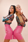 Picture of 2 sisters gorgeous happy smiling blonde and brunette sexy young women sensual girl friends standing together in pink skirts smiling sending kisses and looking at camera on ivory background — Stock Photo