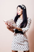 Closeup portrait of beautiful pinup girl brunette cute young woman in polka dot white dress reading book on light background picture — Stock Photo