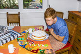 Boy blowing out his birthday candles at the cake — Stock Photo