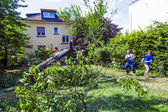 Father and sun cutting a tree in the garden — Stock Photo