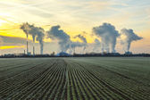 Chimneys and smoke of industry plant with fields in sunrise — Stock Photo