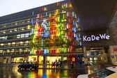 BERLIN - APRIL 4: The famous shopping street Kurfuerstendamm with KADEWE in neon lights on April 4, 2012 in Berlin, Germany. The Kurfurstendamm, is one of the most popular German shopping streets. — Foto de Stock