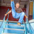Man jumping down the stairs of an old waterless pool - Stock Photo