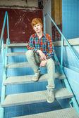 男孩坐在楼梯上的一个旧的无水游泳池 — 图库照片