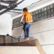 Boy has fun riding his scooter in the skate hall - Foto Stock
