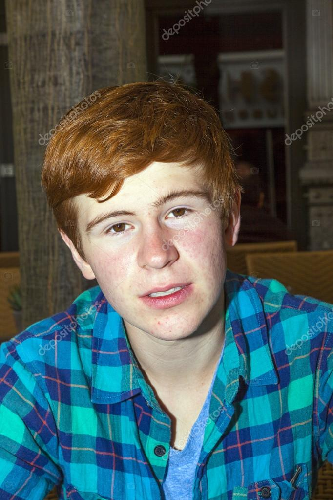 young teenage boy with red hair sitting at a table - Stock Photo