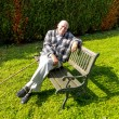 Old man enjoys sitting on a bench in his garden — Stock Photo #13594001