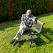 Old man enjoys sitting on a bench in his garden — Stock Photo #13594111