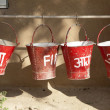 Red fire buckets filled with sand  to protect in case of fire - Stock Photo