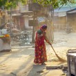 Indian women of fourt class in brightly colored clothing cleans - Stock Photo