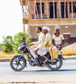 Mother, father and small child riding on scooter through busy hi — Stock Photo