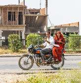Husband with his wife riding on scooter through highway street — Stock Photo