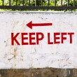 Stock Photo: Keep left sign painted at a wall