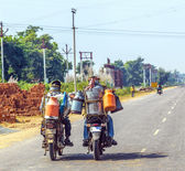 Men riding motorbike with cans of milk — Stok fotoğraf
