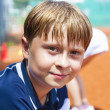 Child looks happy and satisfied after the tennis match - Stock Photo