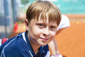 Child looks happy and satisfied after the tennis match — Stock Photo