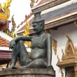 Stock Photo: Sitting man on a stone capital in the Grand Palace, Bangkok