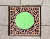 A manhole cover in the street to enter the canalisation — Stock Photo