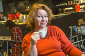 Nice lady enjoys a cup of coffee in a coffee bar — Stock Photo