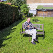 Old man enjoys sitting on a bench in his garden — Stock Photo