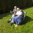 Elderly couple sitting in their garden and enjoy life — Stock Photo #17387153