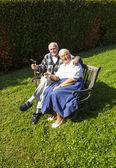 Elderly couple sitting in their garden and enjoy life — Stock Photo