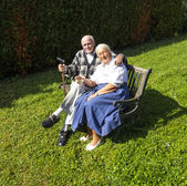 Elderly couple sitting in their garden and enjoy life — Stock Photo