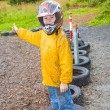 Happy boy with helmet at kart trail — Stock Photo #17418479