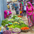 Vendors sell goods in a vegetable street market - 