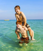 Brothers are enjoying the clear warm water in the ocean and play — Stock Photo