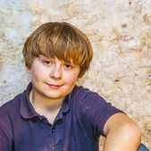 Cute young boy with old brick background — Stock Photo