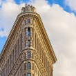 Stock Photo: Facade of the Flatiron building with iron statue of Man on the