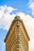 Facade of the Flatiron building with iron statue of Man on the — Stock Photo