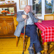 Old Grandfather sitting with his walking stick at the table - Stock Photo