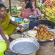 Indian women in brightly colored saris selling bread and crispy - Stock Photo