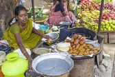 Indian women in brightly colored saris selling bread and crispy — Stock Photo