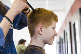 Boy at the hairdresser, she is cutting - close-up with selective — Stock Photo