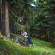 Downhill biker jumps over ramp in forest — Stock Photo #18413539