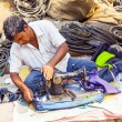 Stock Photo: ORISSA, INDI- NOV 10 - Indimen tailors run their sewing mac