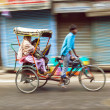 Rickshaw rider transports passenger early morning — Stock Photo #18526757