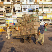 Rickshaw rider transports cargo — Stock Photo