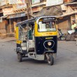 Auto rickshaw taxi driver with passengers in operation - Stock Photo
