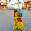 Indian woman carries heavy load on her head - Stock Photo