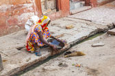 Woman tries to find gold dust in the canalisation — Stock Photo