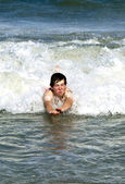 Smart boy at the beach has fun in the waves — Stock Photo